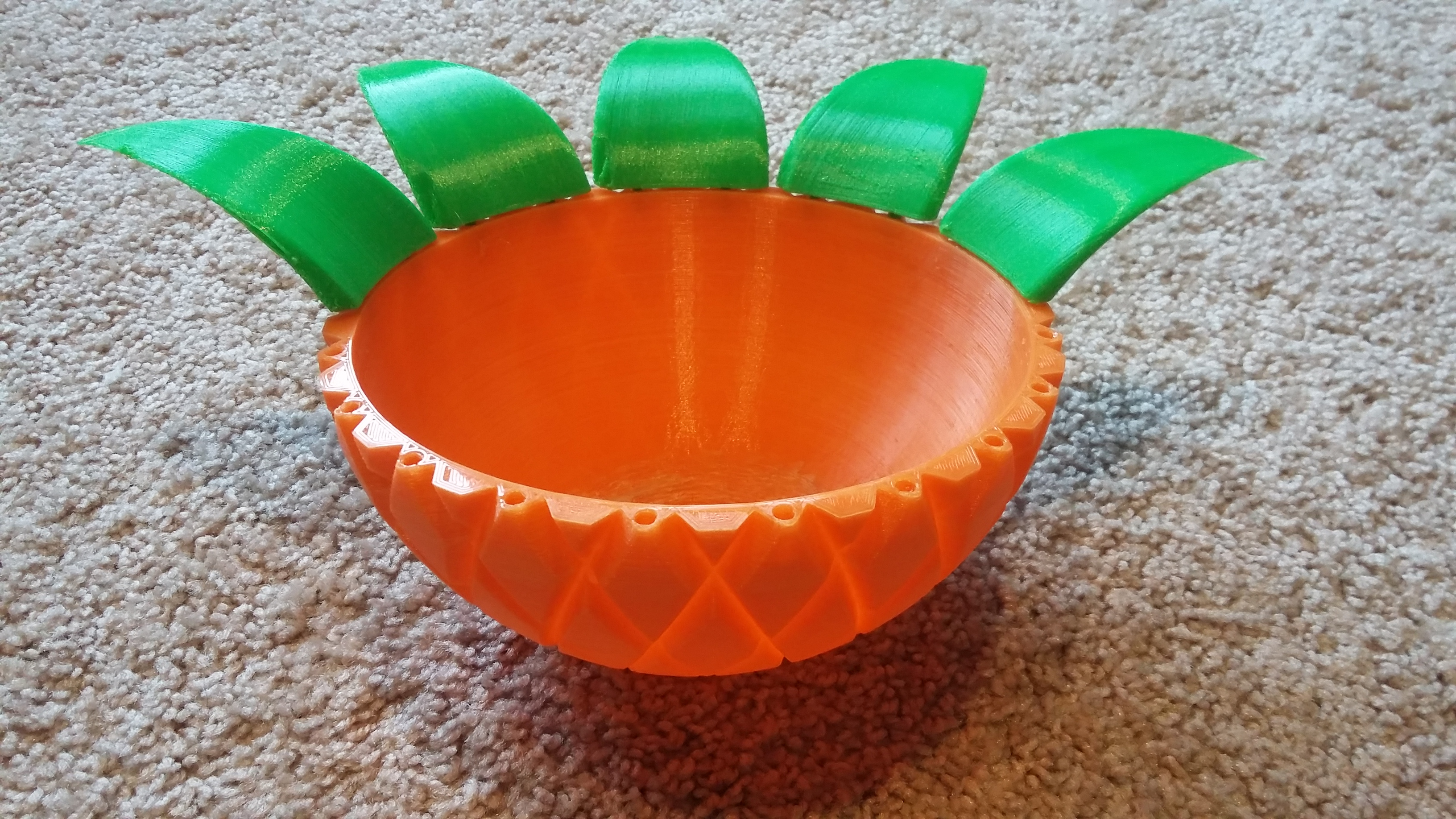 Pineapple-inspired bowl (orange) with green leaves surrounding the edge. Only five of the 10 leaves are finished.