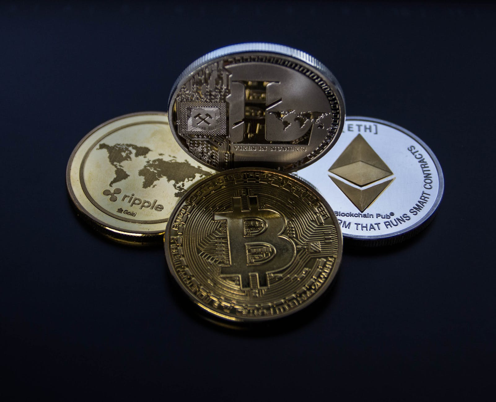 four assorted cryptocurrency coins