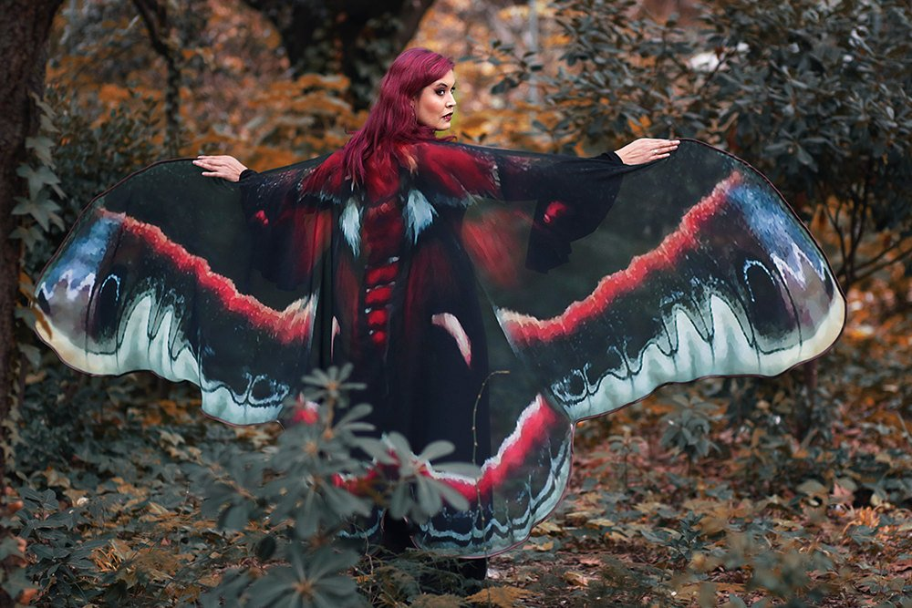 Person wearing a black, white, and crimson cape patterned like moth wings. Cape is wider than armspan in width, makeing the wearer appear to have moth wings.