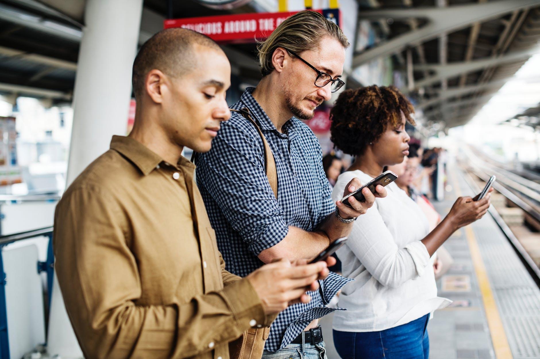 three person holding smartphones