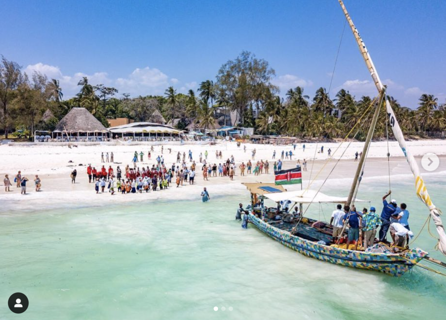 A muli-colored sailboat sits in shallow water just off a white, sandy beach. Many people are on the boat and the shore. A Kenyan flag flies high above the solar panel on the boat.