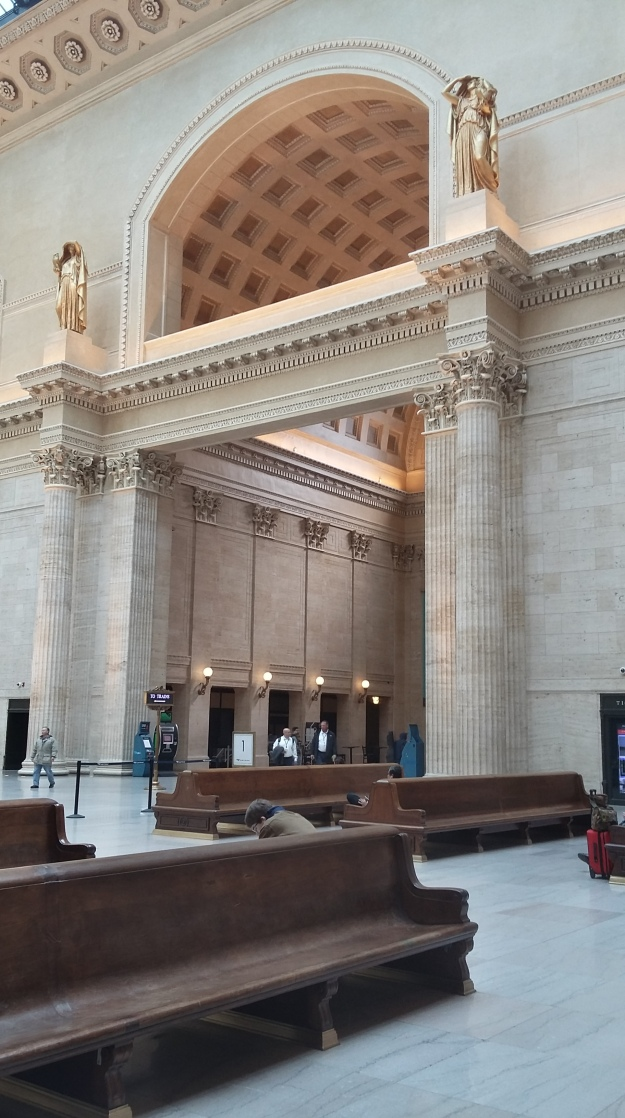 Photo showing the large, open Grand Hall of Chicago's Union Station including two golden, greco-roman statues guarding the entrance to the train departure area