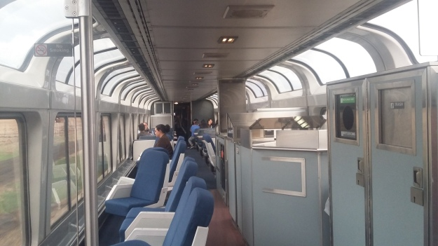 The interior of an Amtrak observation car. Sideways seats face large floor-to-ceiling windows