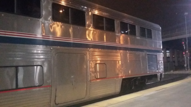 A double-decker Amtrak Superliner car; windows dot the top deck of the car while the bottom features an entry hatch and ventillation grates