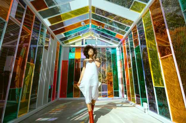 photo of smiling woman in white dress and brown boots posing in multicolored glass house