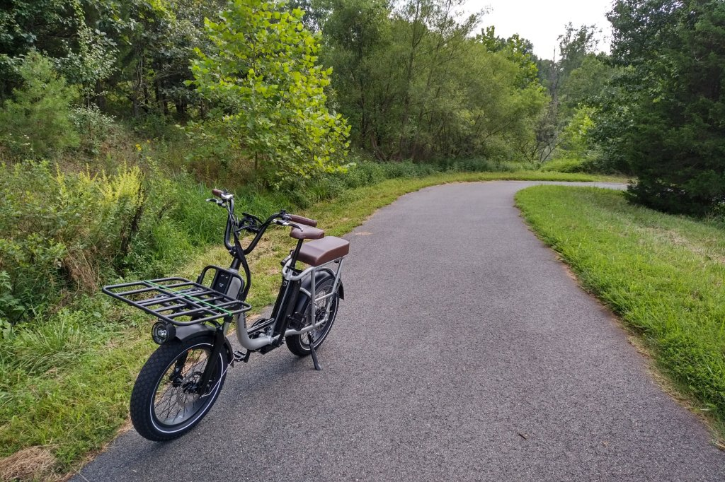 A silver bike sitting on a trail in a wooded area.
