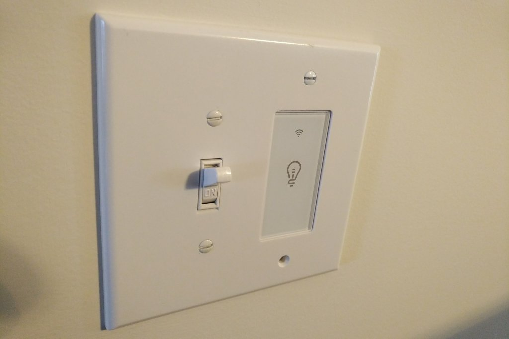 A white touch switch mounted next to a traditional white toggle switch.