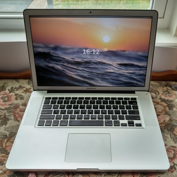 """A 15"""" MacBook Pro Laptop. It is aluminum with black keys on the keyboard. It is sitting on a floral print bench near a window."""
