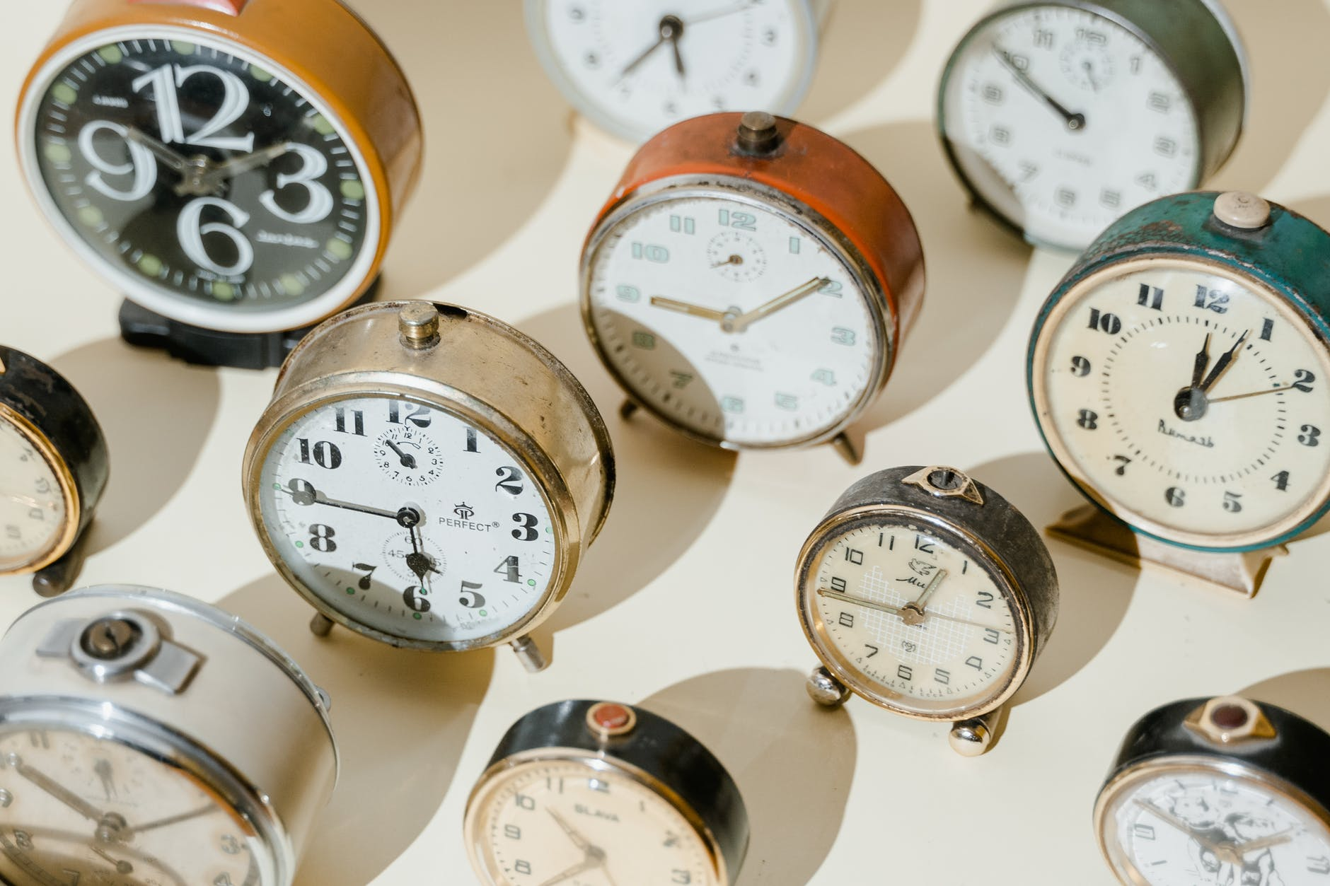 A photo of several vintage clocks lined up in rows.
