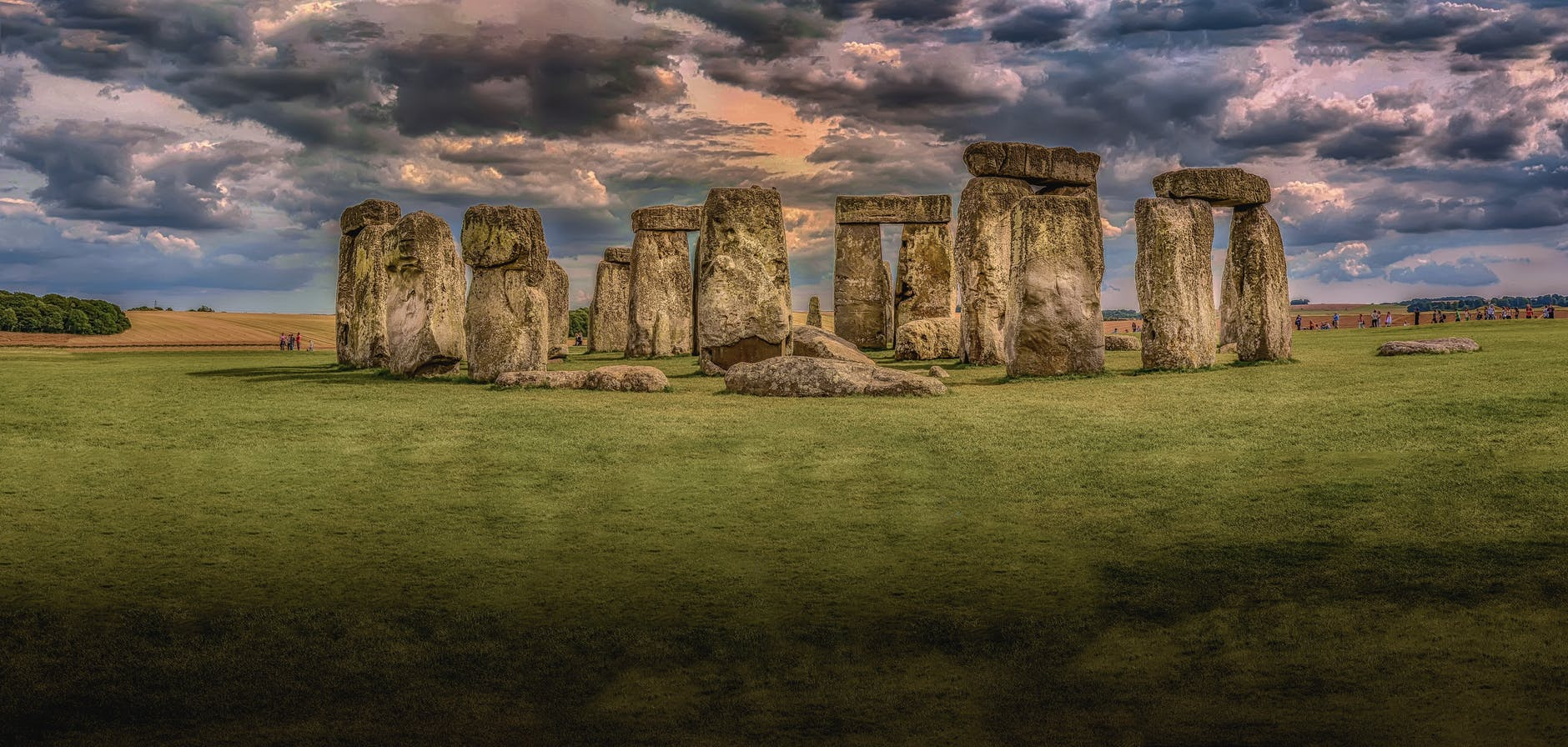An image of Stonehenge. Clouds hang over the monumental stones and the grass is green.