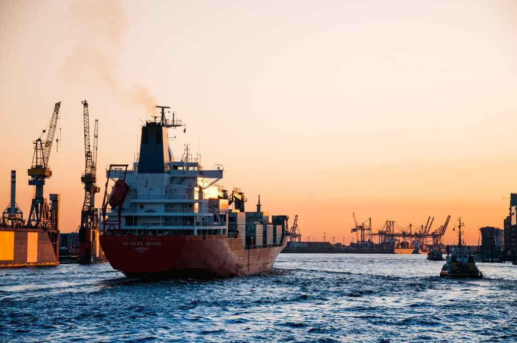 A cargo ship sails down a channel next to a tug boat. A series of cranes dot the sides and background.