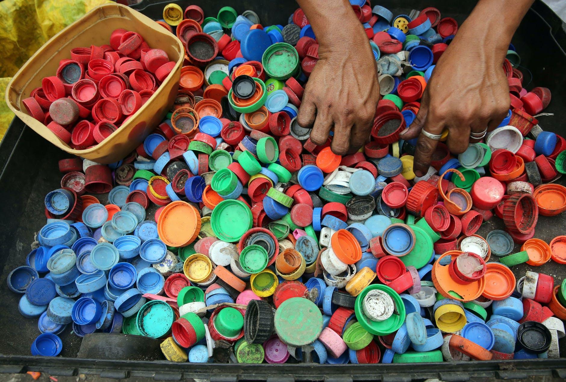 Hands reach into a bin full of soda bottle caps.